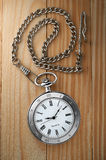 Vintage pocket watch with chain on table Royalty Free Stock Photos