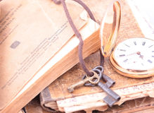 Vintage pocket watch closeup. Antique vintage gold pocket watch and watch three vintage keys closeup on a background of old books Stock Photos