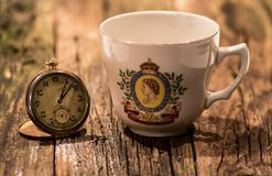 Vintage Pocket Watch And Commemorative Tea Cup stock images
