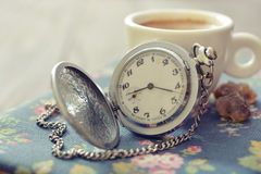 Vintage pocket watch. With cup of coffee on old book closeup royalty free stock photos