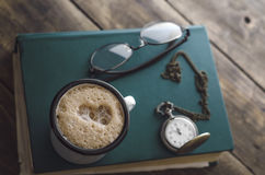 Vintage pocket watch with cup of coffee on old book Royalty Free Stock Photos
