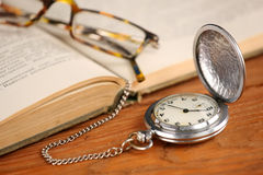 Vintage pocket watch glasses  and open old book Stock Photo