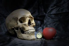 Vintage pocket watch with heart and human skull on black background, Concept love and time, still life photography.  stock photo