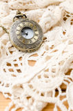 Vintage pocket watch with lace on wooden background Stock Photo