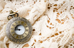 Vintage pocket watch with lace on wooden background Stock Images
