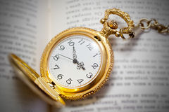 Vintage pocket watch lying on the book, retro style Stock Photography