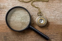 Vintage pocket watch with magnifying glass on wooden background Stock Photos