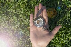 Vintage pocket watch in male hand on a background of green grass. Steampunk watch. The clock mechanism is partially visible royalty free stock image