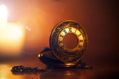 Vintage pocket watch near few lighting candles on dark backgroun Royalty Free Stock Image