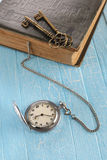 Vintage pocket watch, old book and a brass key Stock Image