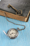 Vintage pocket watch, old book and a brass key Stock Photography