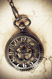 Vintage pocket watch on old map. Vintage clock on antique map. Geographical discovery concept Stock Images