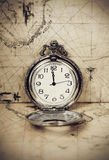 Vintage pocket watch on old map. Vintage clock on antique map. Geographical discovery concept Royalty Free Stock Photography