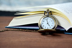 Vintage pocket watch and open book. Stock Photography