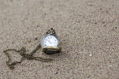 Vintage pocket watch is on the sand. Stock Images