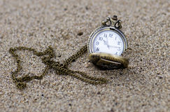 Vintage pocket watch is on the sand. Royalty Free Stock Photos