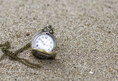 Vintage pocket watch is on the sand. Stock Image