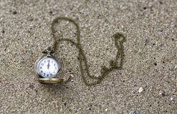 Vintage pocket watch is on the sand. Royalty Free Stock Photography