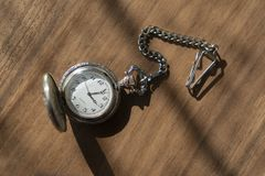 Vintage pocket watch with shadow on wooden background under beam of light royalty free stock image