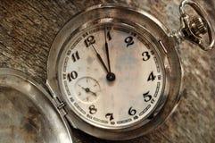 Vintage pocket watch on weathered wood background. Stock Image
