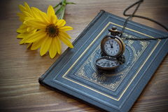 Vintage pocket watch and yellow flower lying on the old book Stock Photo