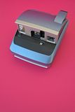 Vintage polaroid camera. Vintage blue polaroid camera in pink retro background Stock Images