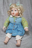 Vintage porcelain doll blonde on gray fabric background Stock Image