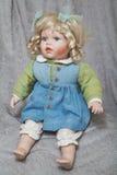 Vintage porcelain doll blonde on gray fabric background Stock Image