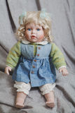 Vintage porcelain doll blonde on gray fabric background Royalty Free Stock Photography