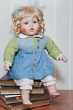 Vintage porcelain doll blonde sitting on stack of books Stock Photo