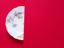 Vintage porcelain plate on red background. Royalty Free Stock Images