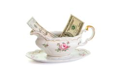Vintage porcelain sauce-boat with dollar bills Stock Photos