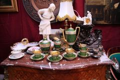 Vintage porcelain tea sets and interior items on an old chest of drawers stock image