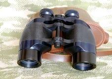 Vintage Porro prism black binoculars on camouflage background Royalty Free Stock Photo