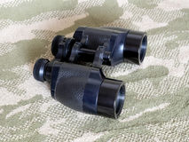 Vintage Porro prism black binoculars on camouflage background Stock Photos