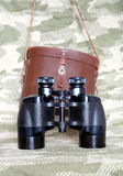 Vintage Porro prism black binoculars on camouflage background. Vintage military Porro prism black color binoculars with brown leather carry case with strap on stock images