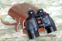 Vintage Porro prism black binoculars with case on camouflage background. Vintage Porro prism black color army binoculars with brown leather carry case with strap royalty free stock images