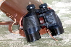 Vintage Porro prism black binoculars with case on camouflage background. Vintage Porro prism black color military binoculars and brown leather carry case with stock photo