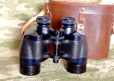 Vintage Porro prism black binoculars with case on camouflage background. Vintage Porro prism black color military binoculars and brown leather carry case with stock image