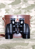 Vintage Porro prism black binoculars with case on camouflage background. Vintage english military Porro prism black color binoculars with brown leather carry royalty free stock image