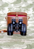 Vintage Porro prism black binoculars with case on camouflage background Royalty Free Stock Photos