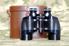 Vintage Porro prism black binoculars with case on camouflage background. Vintage military Porro prism black color binoculars with brown leather carry case with stock image