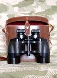Vintage Porro prism black binoculars with case on camouflage background Stock Photos