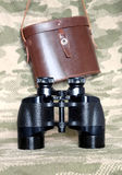 Vintage Porro prism black binoculars with case on camouflage background. Vintage military Porro prism black color binoculars with brown leather carry case with stock photography