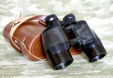 Vintage Porro prism black binoculars with case on camouflage background. Vintage military Porro prism black color binoculars with brown leather carry case with royalty free stock photo