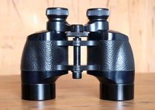 Vintage Porro prism black binoculars on woden background stock photography