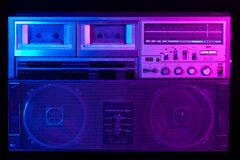 Vintage portable stereo boombox cassette recorder from 80s with reflection of blue and pink neon light