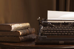 Vintage portable typewriter with a piece of paper and vintage bo Stock Photography