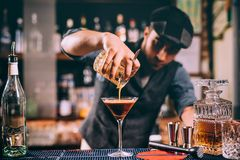 portrait of bartender creating cocktails at bar. Close up of alcoholic beverage preparation Royalty Free Stock Photography