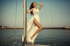 Vintage portrait of beautiful elegant woman in luxury long dress. Standing on the yacht. High fashion photo Stock Photos